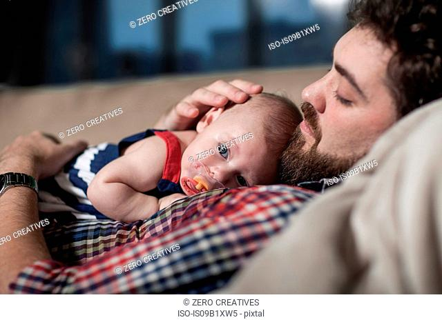 Father comforting baby girl at home