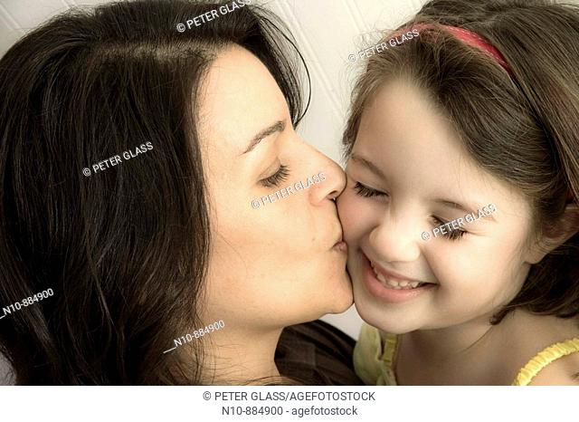 Mother kissing her young daughter.  Model and Property Released