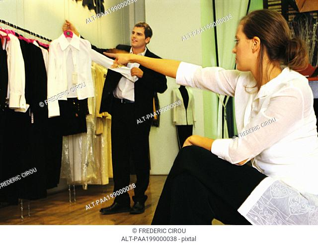 Man holding up woman's blouse, woman sitting and pointing, in clothing store
