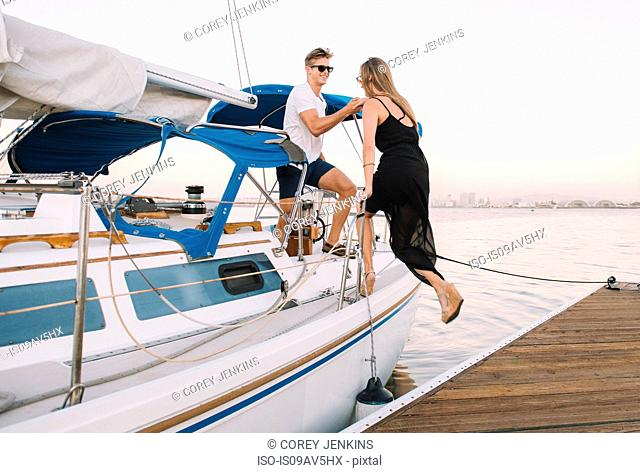 Couple boarding sailboat, San Diego Bay, California, USA