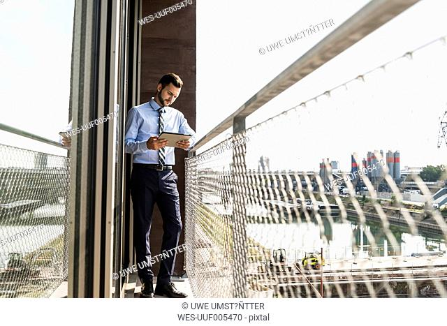 Young businessman standing on balcony looking on digital tablet