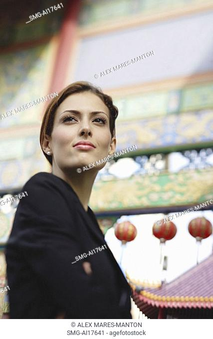 Businesswoman looking away, temple gates in the background