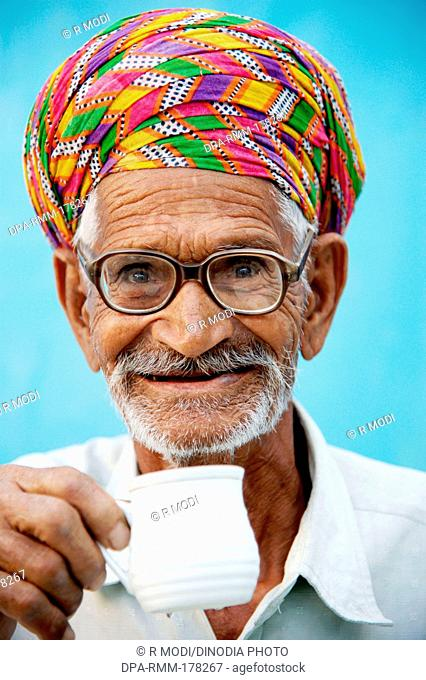 Old man drinking tea wearing glasses and colorful turban Rajasthan India Asia MR#784B