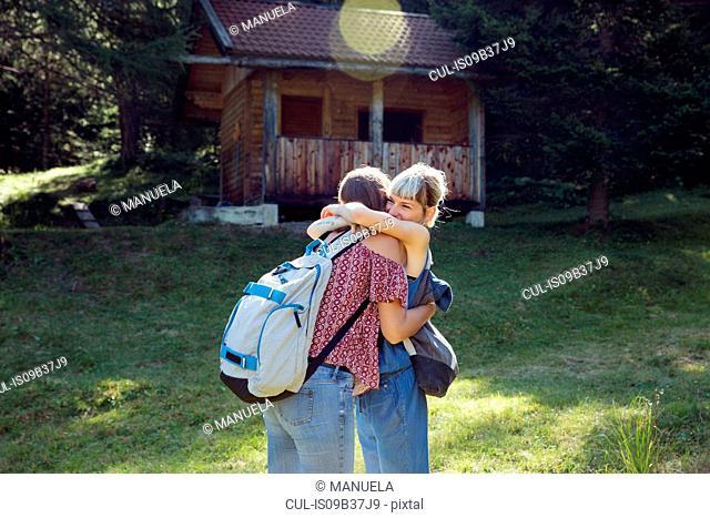 Two female friends hugging in forest glade, Sattelbergalm, Tyrol, Austria