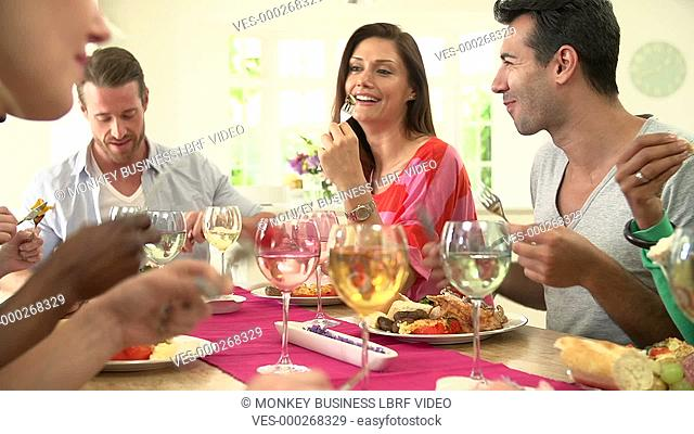 Group of friends sitting and eating meal around table.Shot on Sony FS700 in PAL format at a frame rate of 25fps