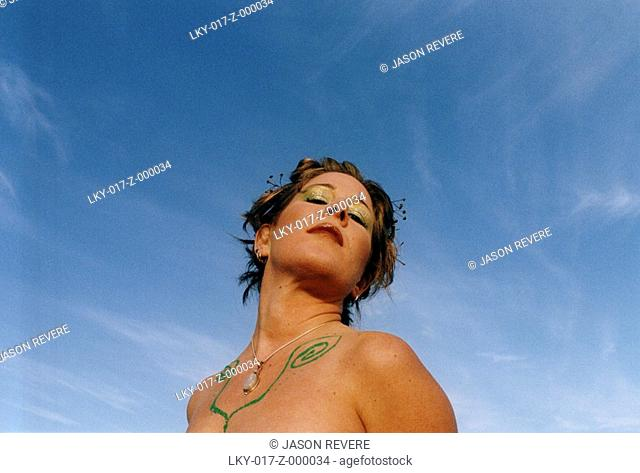 Woman with body paint looks up into blue sky
