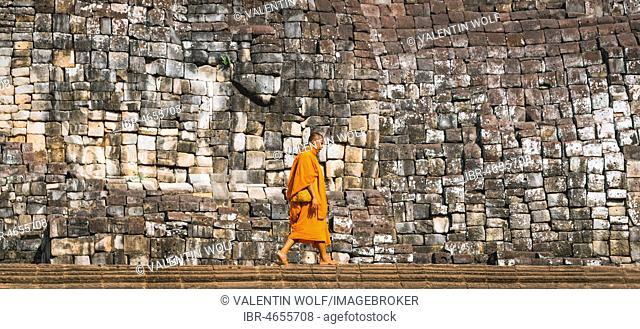 Buddhist monk walks in front of old stone wall, Bayon temple, temple ruin, temple complex, Angkor Wat, Angkor Archaeological Park, Siem Reap Province, Cambodia