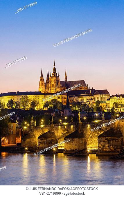 Prague Castle St Vitus Cathedral Charles bridge and Vtlava River illuminated at dusk Czech Republic