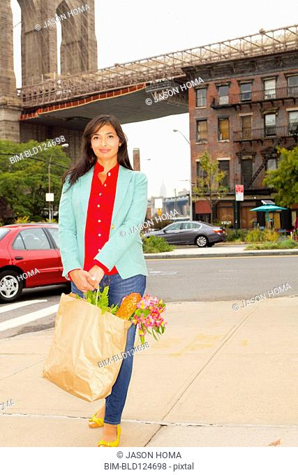 Mixed race woman with shopping bag, New York, New York, United States