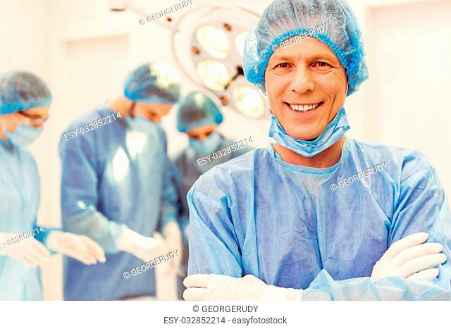 Team surgeons are performing an operation, handsome middle aged doctor is looking at camera and smiling, in a modern operating room