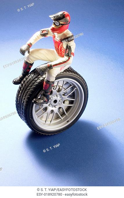 Racing driver figure on miniature wheel