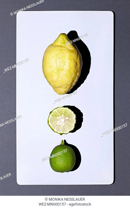 Lemon and whole and sliced lime on white board