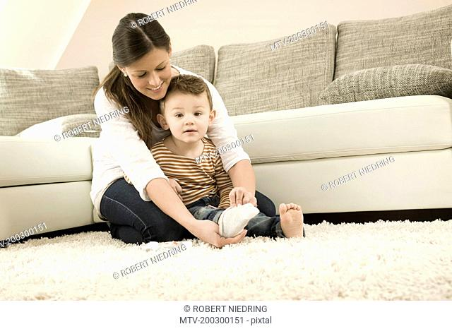Mother putting socks on son, smiling