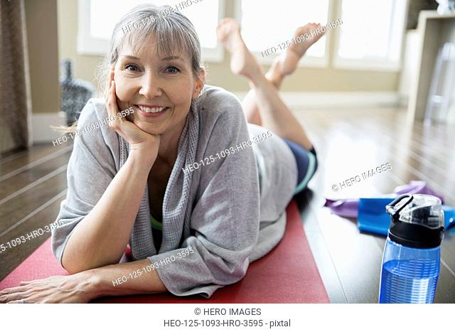 Portrait of smiling woman laying on yoga mat