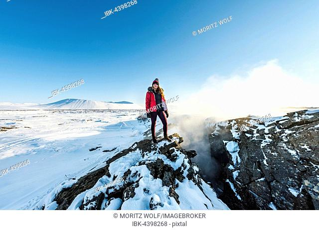 Woman standing at divergent tectonic boundary between North American and Eurasian plates, Mid-Atlantic Ridge, rift valley, Silfra, Krafla, Northern Region