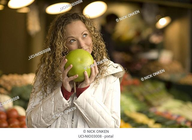Young woman smelling fruit for sale
