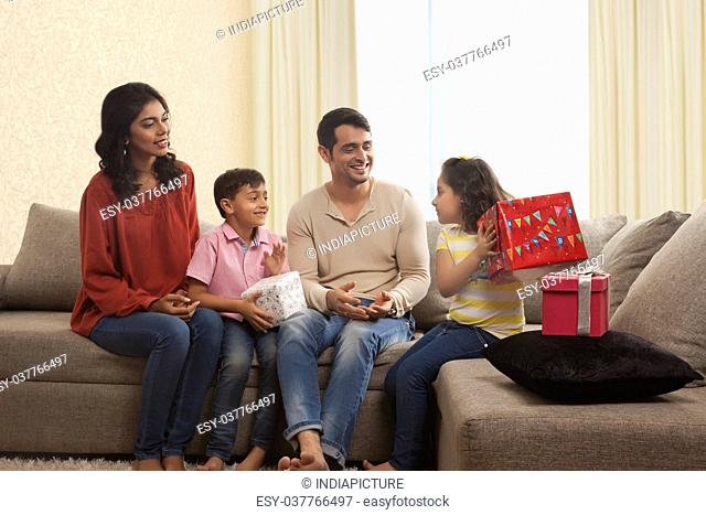 Family with gifts sitting on sofa in living room