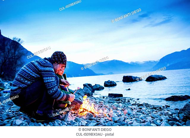 Father and son toasting marshmallows over campfire, Onno, Lombardy, Italy