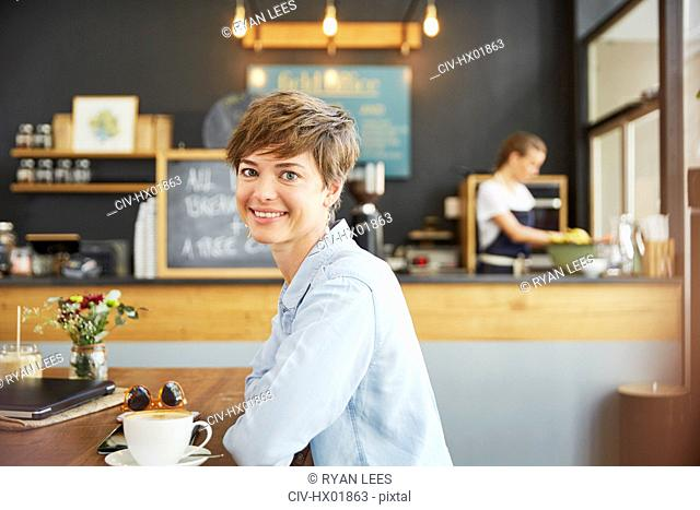 Portrait smiling woman drinking coffee at cafe table