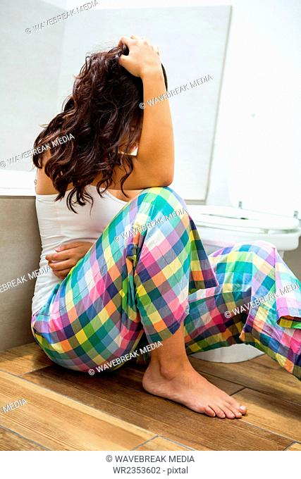 Young woman having stomach pain in bathroom