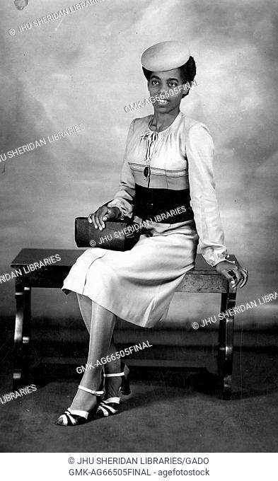 Young African American woman in elegant clothing sitting on a bench and posing for a studio portrait, with a hat and purse, Kentucky, 1920