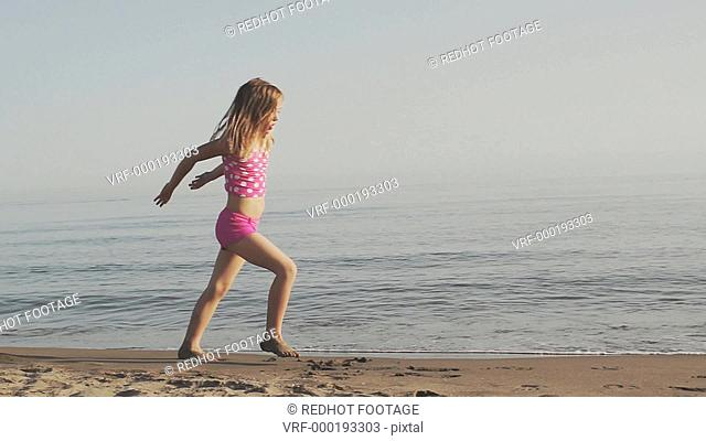 Slow motion of girl doing cartwheels on beach