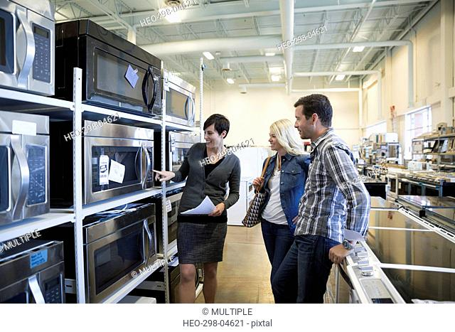 Saleswoman helping couple shopping for microwave in appliance store