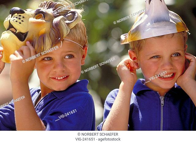 portrait, close-up, two blond 5-year-old twin-boys wearing blue t-shirts with their animal-masks put on their heads  - GERMANY, 30/05/2004