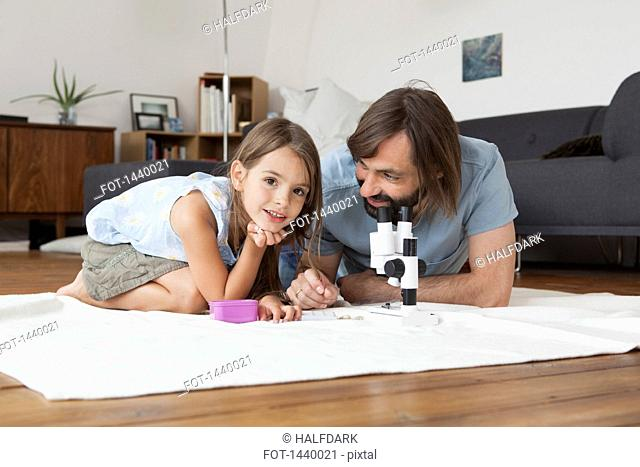 Father and daughter using microscope on carpet at home