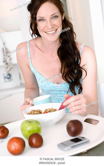 Portrait of a mid adult woman having breakfast and smiling