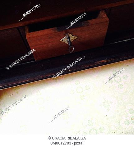 Old drawer of a wooden cabinet with a key in the lock