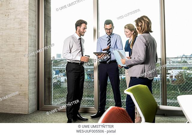 Business people with digital tablet and documents talking at the window