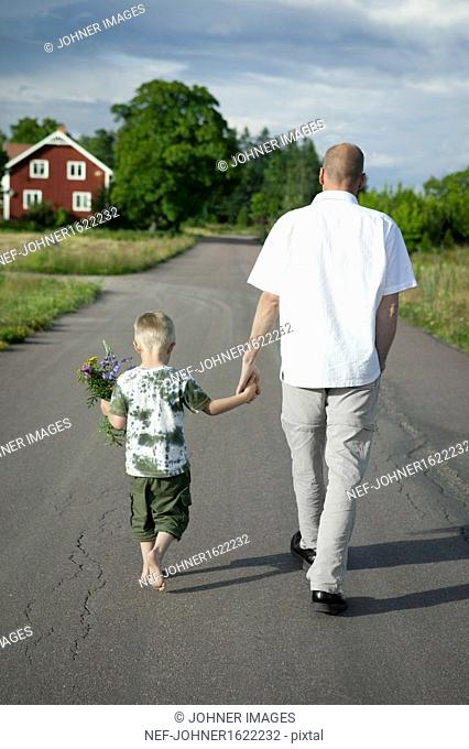 Father walking with son on road, boy holding flowers