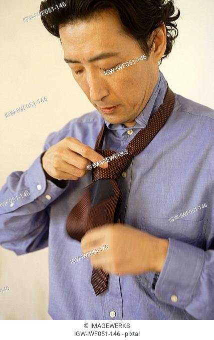 Mature man knotting tie, side view