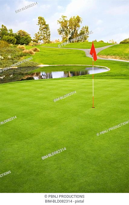 Flag on golf course next to pond