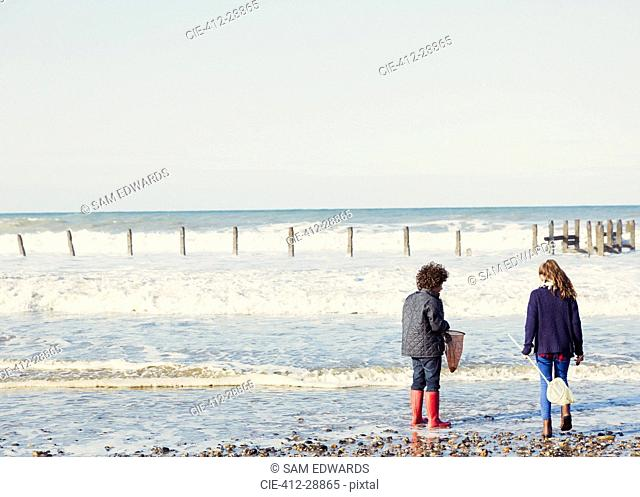 Brother and sister with nets in ocean surf