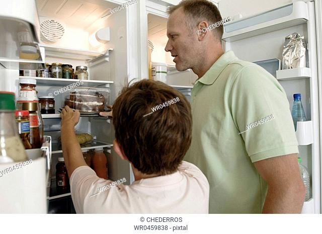 Rear view of a boy taking out cake from a refrigerator with his father standing beside him