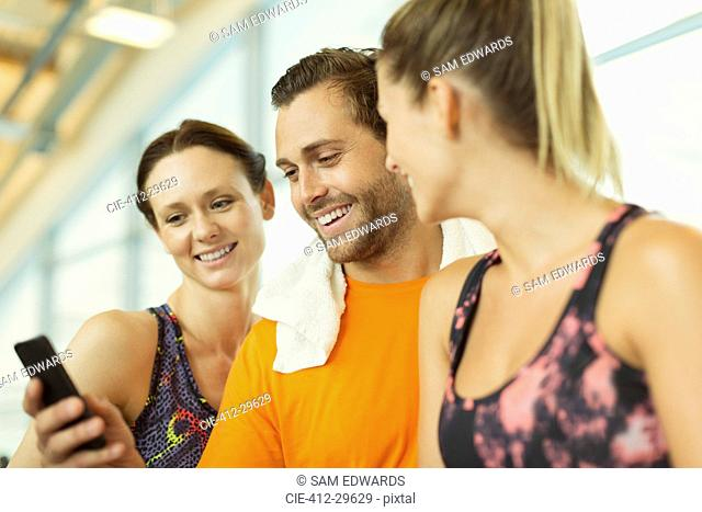 Smiling friends using cell phone at gym