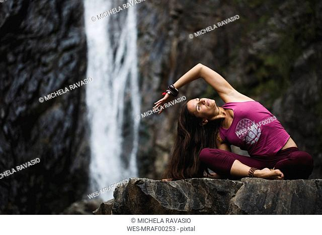 Italy, Lecco, woman doing yoga practice near a waterfall