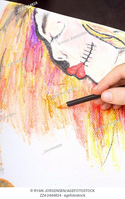 Closeup on the hand of a professional artist illustrating the intricate details and fine lines on a sugar skull girl watercolour sketch