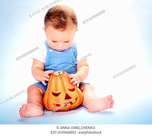 Cute little baby boy sitting in the studio over grey background and with wonder looking on the orange carved pumpkin, happy Halloween day