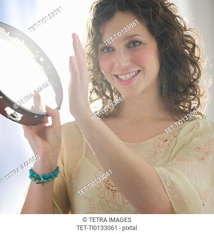 Close up of woman playing tambourine