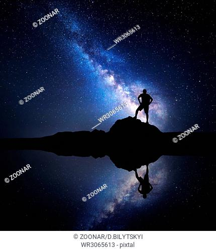 Milky Way and silhouette of a standing man near lake
