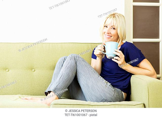 Woman relaxing on sofa and drinking coffee