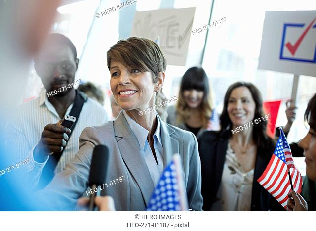 Smiling female politician greeting media and audience