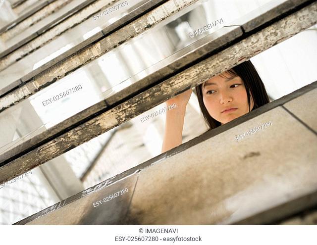 Woman peeking through stairs