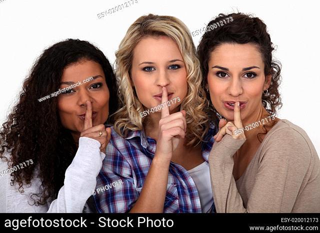Three women making shush gesture