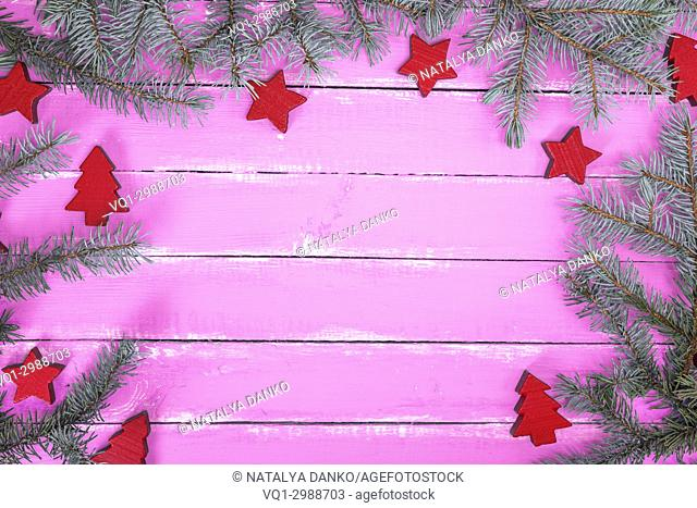 pink wooden background of boards with green spruce branch and Christmas decor, empty space