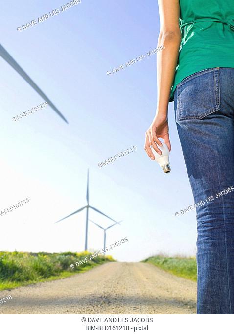Indian woman holding light bulb near wind turbines