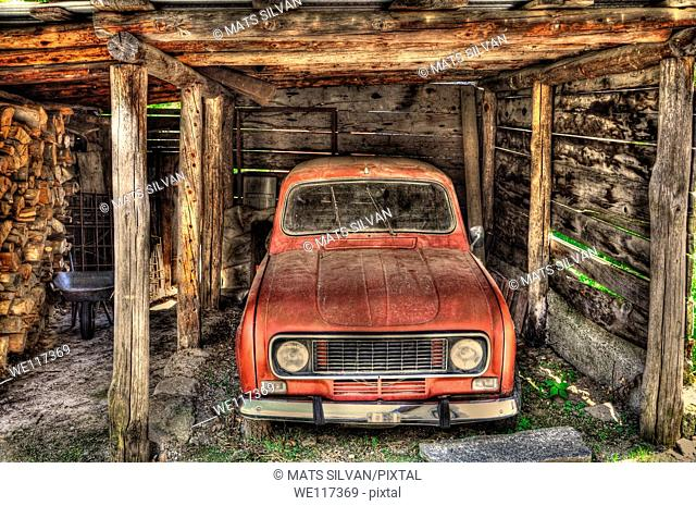 Old red car in a wood garage
